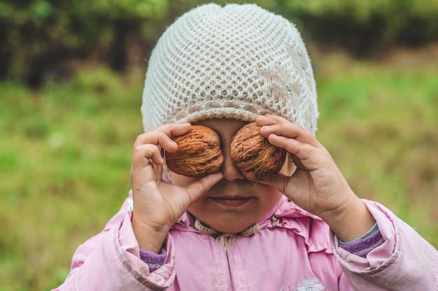 Grając na zewnątrz śliczna mała dziewczynka trzyma orzechy przed nią. zbiory orzechów. jesień w ogrodzie, śliczna dziewczynka i duże orzechy.