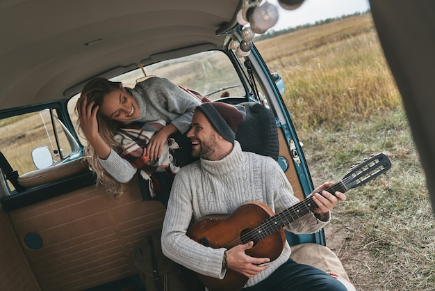 Grając z jego sercem. przystojny młody mężczyzna gra na gitarze dla swojej pięknej dziewczyny, siedząc w mini vanie w stylu retro
