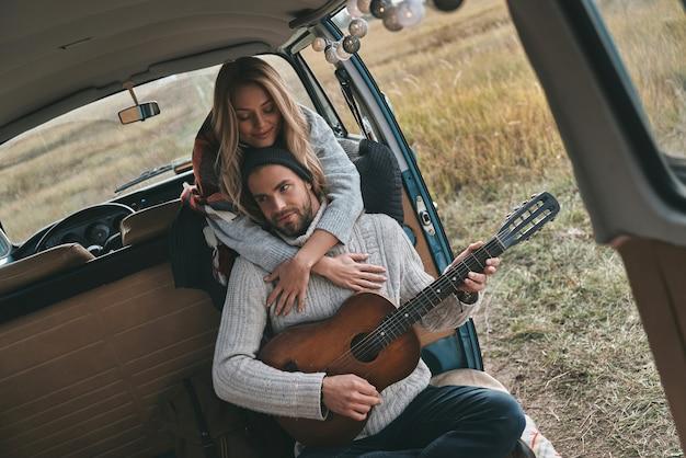 Gram romantyczną piosenkę. przystojny młody mężczyzna gra na gitarze dla swojej pięknej dziewczyny, siedząc w mini vanie w stylu retro