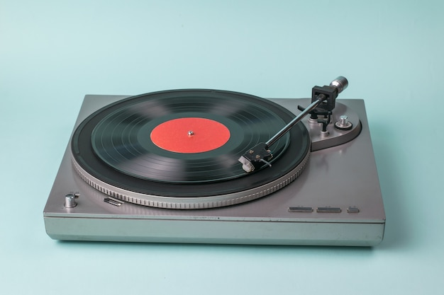 Gramofon szary na niebieskim tle. sprzęt retro do odtwarzania muzyki.
