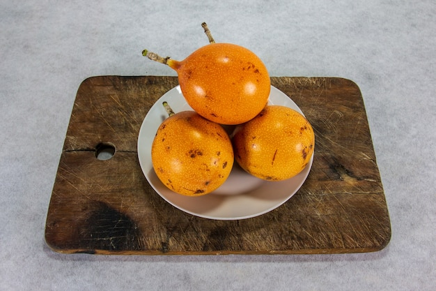 Granadilla cztery peruwiańskie owoce o twardej skórce na porcelanowym talerzu i drewnianej desce