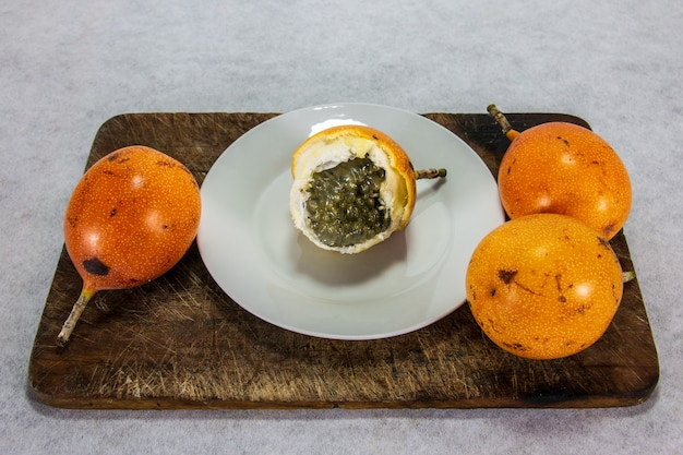 Granadilla owoc peruwiański o twardej skórce na porcelanowym talerzu i drewnianej desce