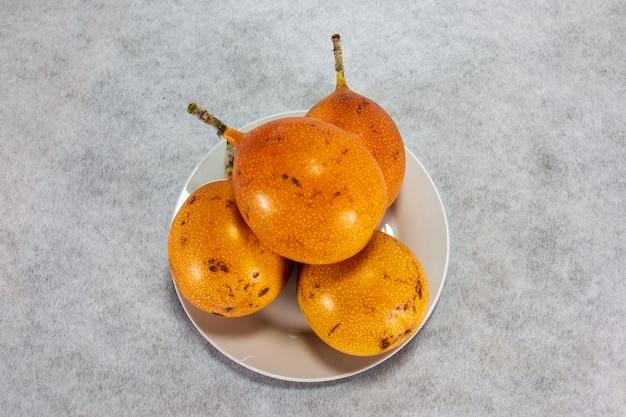 Granadilla trzy peruwiańskie owoce o twardej skórce na porcelanowym talerzu i drewnianej desce