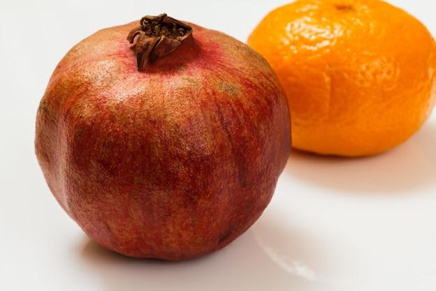 Granat i mandarynka na białej powierzchni