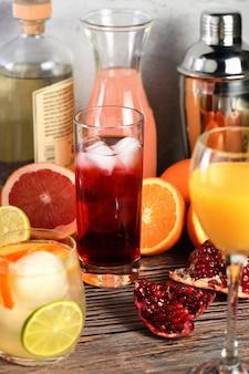 Granat koktajl gin na stole wśród owoców cytrusowych i napojów.