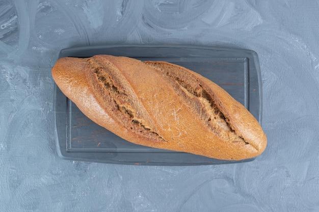 Granatowa drewniana deska pod pojedynczym bochenkiem chleba na marmurowym stole.