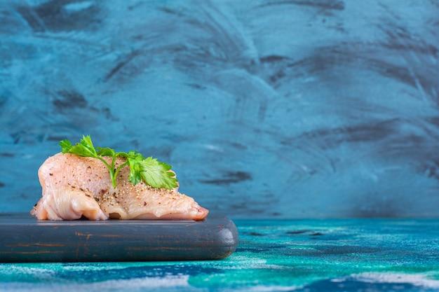 Granatowe listki, liście sałaty z krążkiem cebuli obok piersi kurczaka na drewnianej tacy