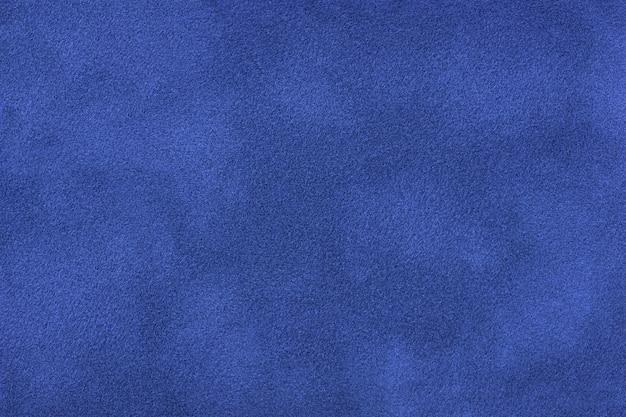 Granatowe matowe tło zamszowej tkaniny, zbliżenie. aksamitna tekstura bezszwowych tekstyliów szafirowych, makro. struktura tła z filcu w kolorze indygo.