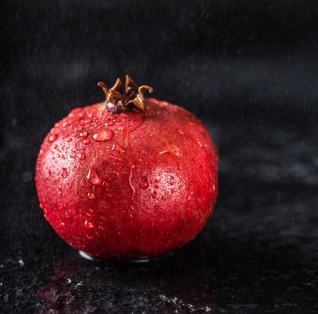 Granatowiec czerwony sok na ciemnym stole. przydatny granat