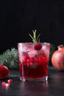 Granatowy świąteczny koktajl z rozmarynem, szampanem, sodą klubową na czarnym stole. ścieśniać. format pionowy.