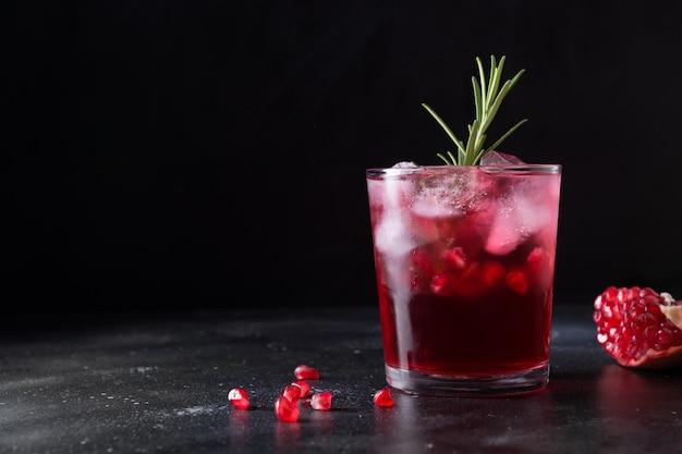 Granatowy świąteczny koktajl z rozmarynem, szampanem, sodą klubową na czarnym stole. ścieśniać.