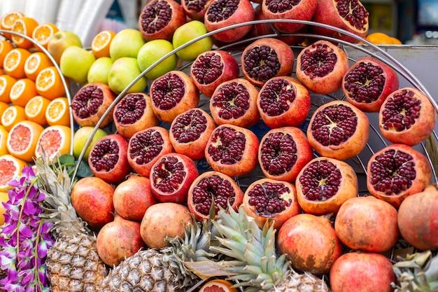 Granaty pomarańcze ananasy jabłka na gablocie baru ze świeżo wyciskanymi sokami
