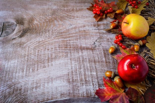 Granica jabłka, jagody i spadek liście na nieociosany drewnianym