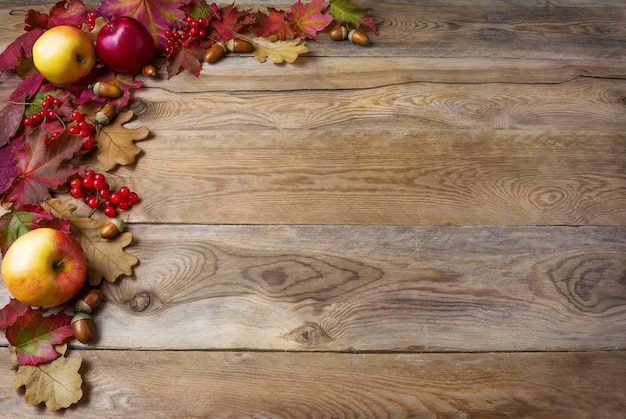 Granica jabłka, żołędzie, jagody i spadek liście na starym drewnianym