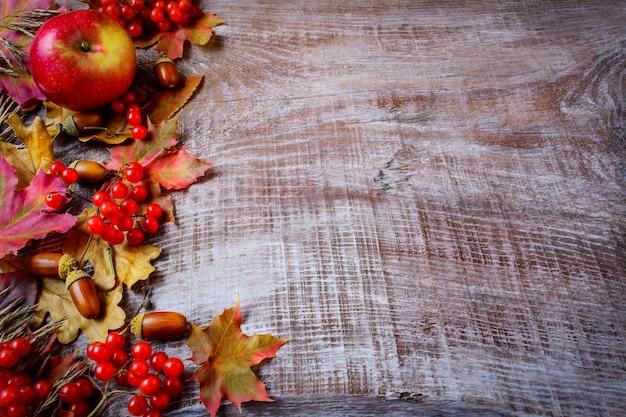 Granica owoców i spadek liści na ciemnym drewnianym