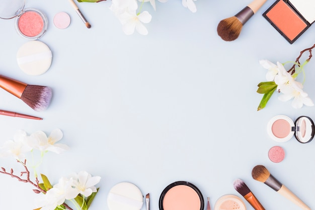 Granica robić z kosmetyków produktami i kwiatami na błękitnym tle