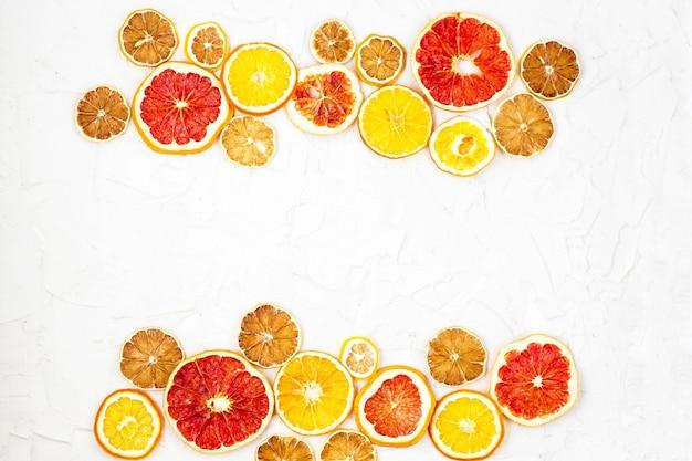 Granica suszonych plasterków różnych owoców cytrusowych na białej powierzchni.