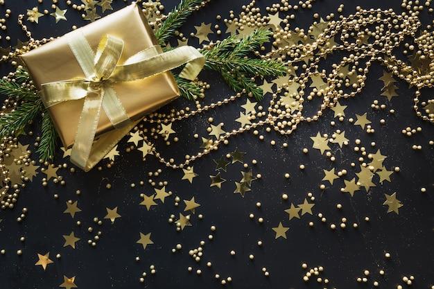 Granica złote pudełko na czarnym tle. prezent gwiazdkowy. leżał płasko. widok z góry. boże narodzenie.