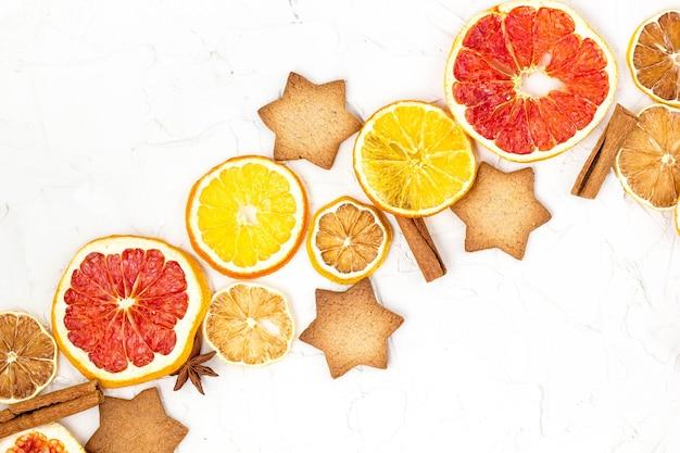 Granicy suszonych plasterków piernika i przypraw korzennych różnych owoców cytrusowych na białym tle z lato. boże narodzenie ramki