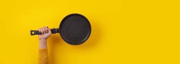 Granitowa patelnia w dłoni na żółtym tle, panoramiczny obraz z miejscem na tekst