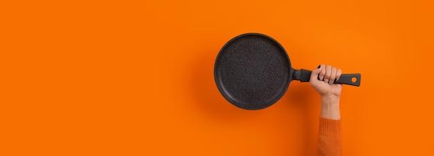 Granitowa patelnia w ręku na pomarańczowym tle, panoramiczna makieta z miejscem na tekst