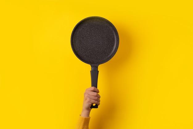 Granitowa patelnia w ręku na żółtym tle