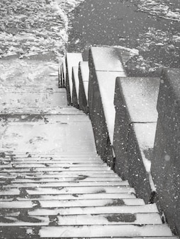 Granitowe schody do zamarzniętej rzeki. dryf lodu na rzece.