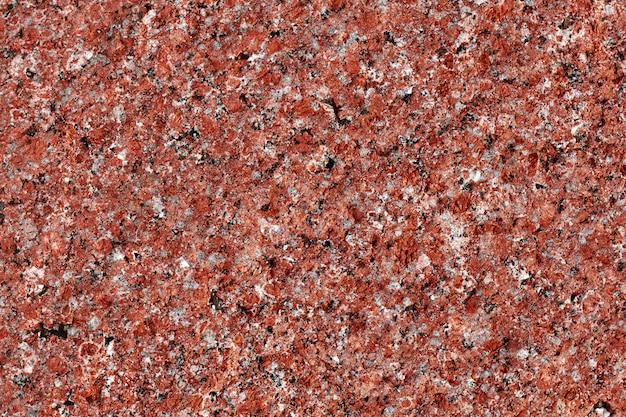 Granitowe tło. tekstura kamienia naturalnego. czerwona powierzchnia. wzór.