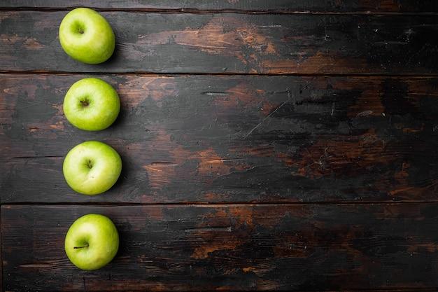 Granny smith apple set, na starym ciemnym rustykalnym tle stołu, widok z góry płasko leżący, z miejscem na kopię tekstu