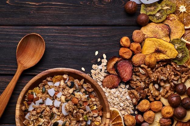 Granola i suszone owoce z orzechami na drewnianym stole