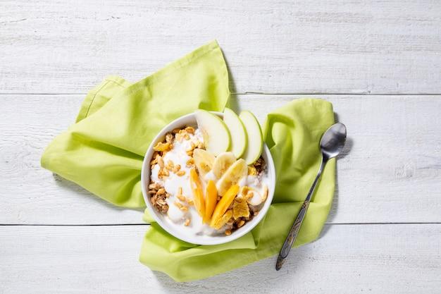 Granola i wegetariański jogurt z plasterkami jabłka, moreli, bananów na białym tle drewnianych.