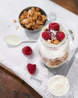 Granola jogurt grecki parfait świeże maliny kokosowe w szklance na drewnianym stole na zewnątrz