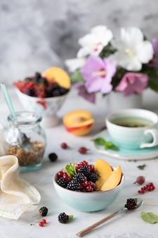 Granola lub musli z jagodami i owocami na zdrowe śniadanie rano z bukietem letnich kwiatów na lekkim stole.