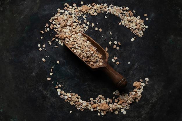 Granola, musli w drewnianej łyżce rozłożone na rustykalnym stole. widok z góry. flat lay