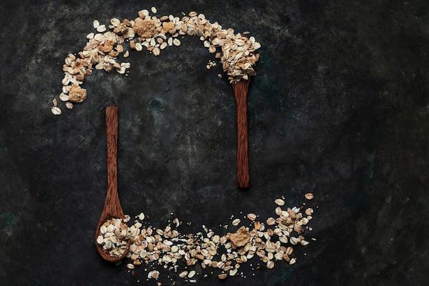 Granola, musli w drewnianych łyżeczkach kokosowych rozłożonych na rustykalnym stole. widok z góry. flat lay