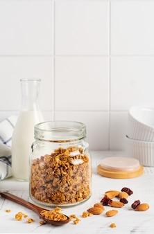 Granola owsiana z butelką mleka, orzechów i suszonych owoców, ceramiczne miseczki do przygotowania zdrowego śniadania na jasnym kuchennym stole. skandynawski biały styl. selektywna ostrość.