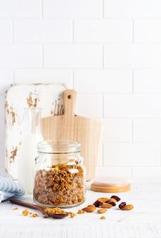 Granola owsiana z orzechami i suszonymi owocami do przygotowania zdrowego śniadania na jasnym kuchennym stole. skandynawski biały styl. selektywne skupienie.