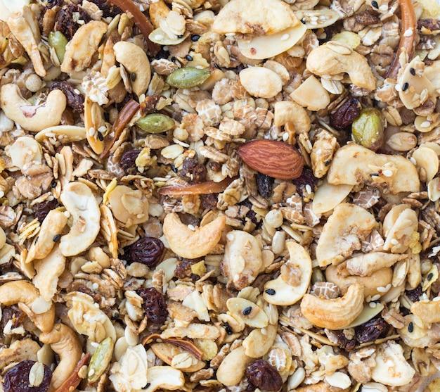 Granola tekstura tło. stos granola z migdałami i ziarnami przed piec.