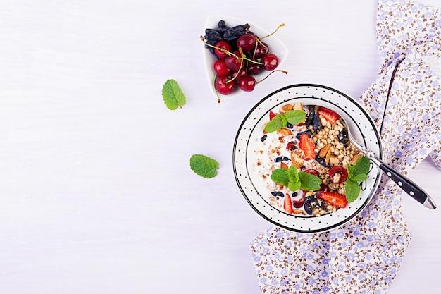Granola, truskawki, wiśnia, wiciokrzew, orzechy i jogurt w misce