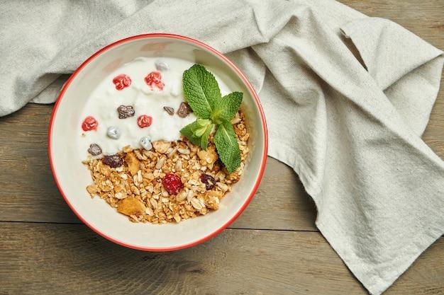 Granola z greckim jogurtem i jagodami w misce z lnianą ściereczką na drewnianej powierzchni. zamknij się z miejscem na tekst. klasyczne śniadanie
