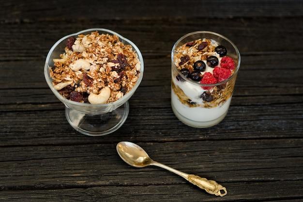 Granola z jagodami i jogurtem na czarnym drewnianym stole. tradycyjne śniadanie amerykańskie