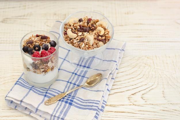 Granola z jagodami i jogurtem na drewnianym stole. tradycyjne śniadanie amerykańskie