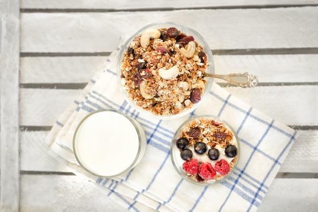 Granola z jagodami i orzechami, szklanka jogurtu na białym ręczniku. tradycyjne śniadanie amerykańskie