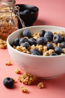 Granola z jagodami w misce na różowym tle. zdrowe jedzenie. widok z boku.