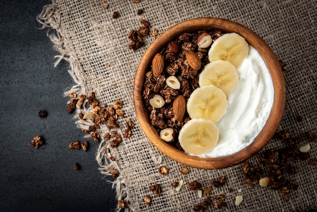 Granola z jogurtem, bananem i orzechami na czarnej powierzchni.