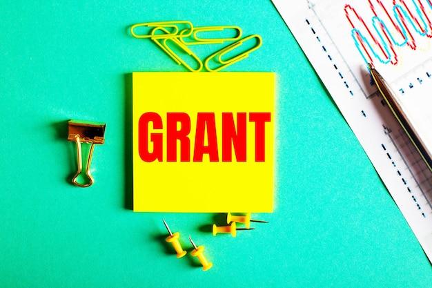 Grant jest napisane na czerwono na żółtej naklejce na zielonej powierzchni w pobliżu wykresu i ołówka