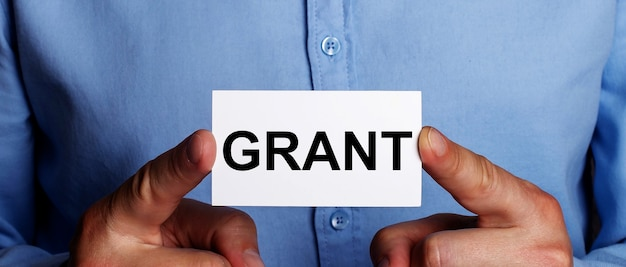 Grant jest zapisane na białej wizytówce w rękach mężczyzny. pomysł na biznes