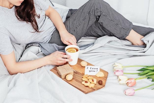 Gratulacje dla twojej ulubionej dziewczyny w walentynki. śniadanie w łóżku. kobieta w piżamie przyjmuje prezenty 14 lutego.