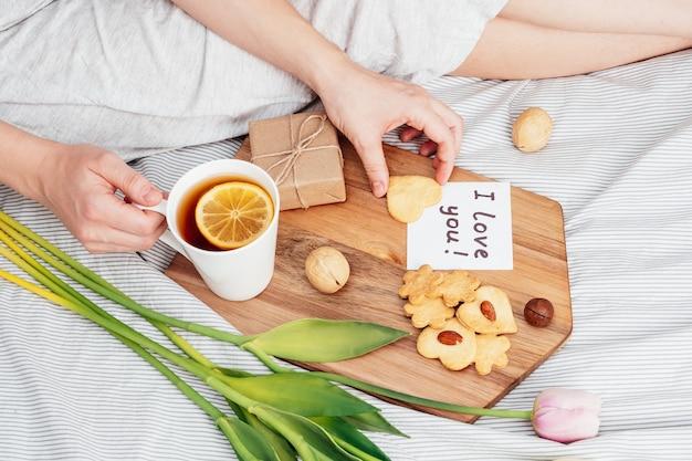 Gratulacje dla ukochanej kobiety w walentynki. śniadanie do łóżka dla dziewczyny w koszuli nocnej. kwiaty i prezent na 14 lutego.