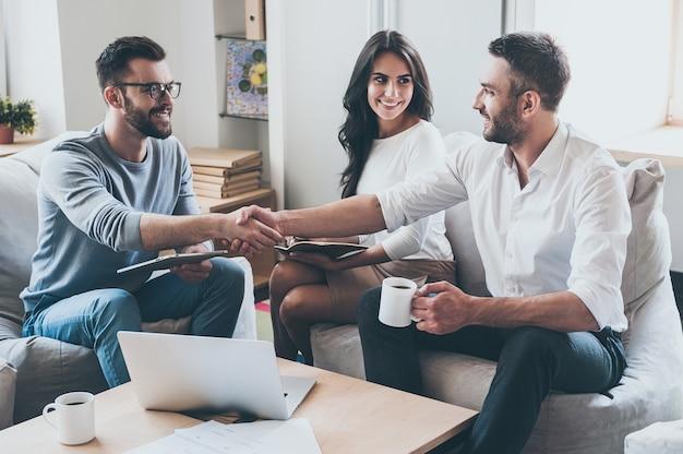 Gratulacje! trzech młodych, wesołych ludzi biznesu siedzących razem przy biurku, podczas gdy mężczyźni ściskają sobie ręce